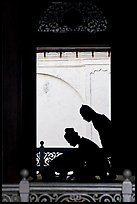 Silhouettes of men bowing in worship, Masjid Kampung Hulu. Malacca City, Malaysia (color)