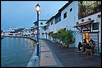 Women relaxing in front of riverside house, dusk. Malacca City, Malaysia (color)