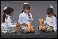 Three little girls in school uniform eating snack. Guadalajara, Jalisco, Mexico
