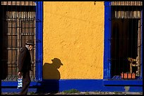 Elderly man walking along a colorful wall, Tlaquepaque. Jalisco, Mexico (color)