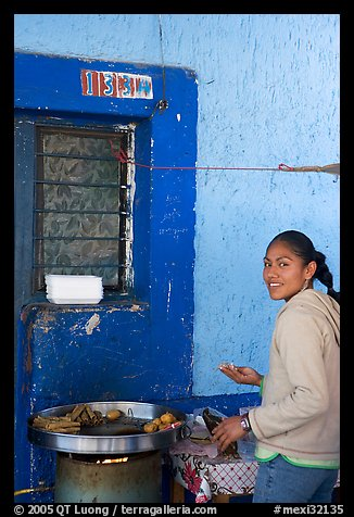 Woman preparing food outside a blue wall, Tonala. Jalisco, Mexico (color)
