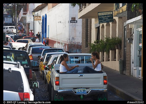 Young women riding in the back of a pick-up truck in a busy street, Puerto Vallarta, Jalisco. Jalisco, Mexico