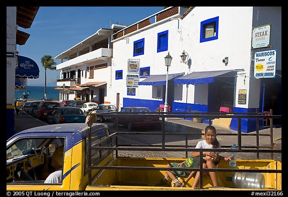 Girl riding in the back of pick-up truck in a street close to ocean, Puerto Vallarta, Jalisco. Jalisco, Mexico