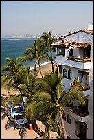 White adobe building with red tile roof,  palm trees and ocean, Puerto Vallarta, Jalisco. Jalisco, Mexico ( color)