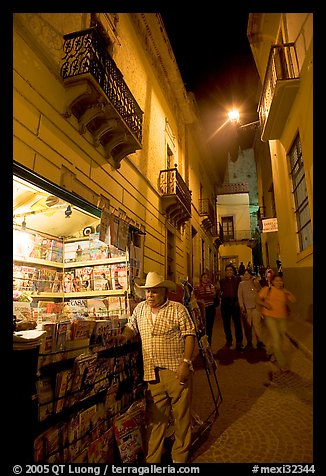 Man at a Newstand booth in a narrow callejone at night. Guanajuato, Mexico (color)
