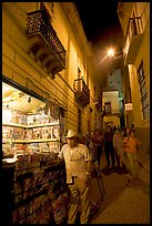 Man at a Newstand booth in a narrow callejone at night. Guanajuato, Mexico ( color)