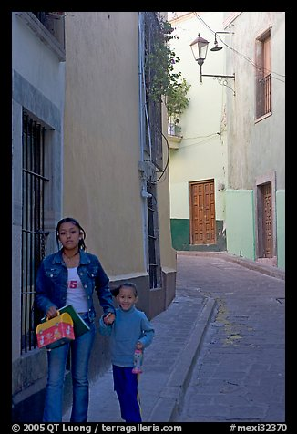 Woman and child walking in a narrow street. Guanajuato, Mexico