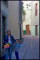 Woman and child walking in a narrow street. Guanajuato, Mexico ( color)