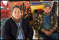 Couple sitting in front of carpets. Guanajuato, Mexico (color)