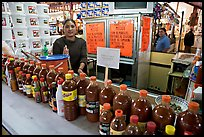 Woman at a booth with lots of chili bottles in Mercado Hidalgo. Guanajuato, Mexico ( color)