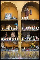 Candles, flowers, and religious offerings in a roadside chapel. Mexico (color)