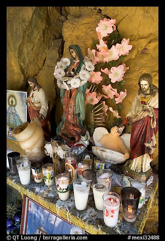 Religious figures and candles in roadside chapel. Mexico (color)