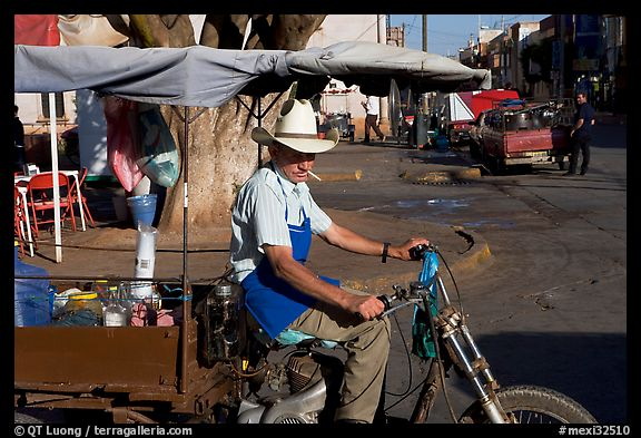 Man with cigarette riding a motorcycle-powered food stand on town plaza. Mexico (color)