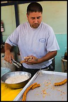 Man coating churros in sugar. Baja California, Mexico ( color)
