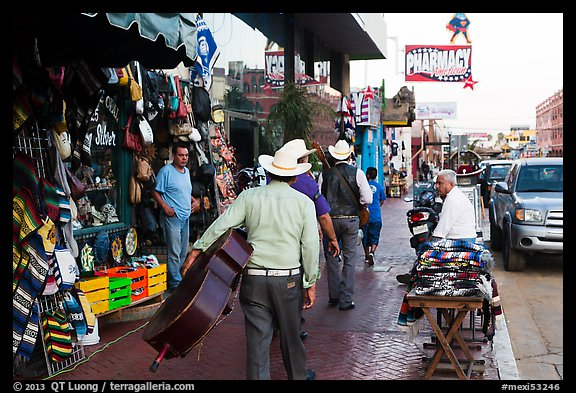 Musicians walking on street, Ensenada. Baja California, Mexico (color)