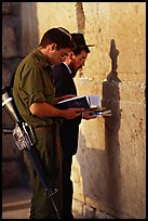 Young soldier and orthodox jew reading prayer  books at the Western Wall. Jerusalem, Israel (color)