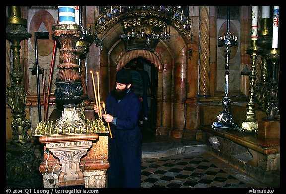 Christian Orthodox priest lighting candles. Jerusalem, Israel