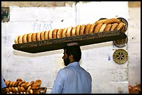 Man carrying many loafes of bread on his head. Jerusalem, Israel