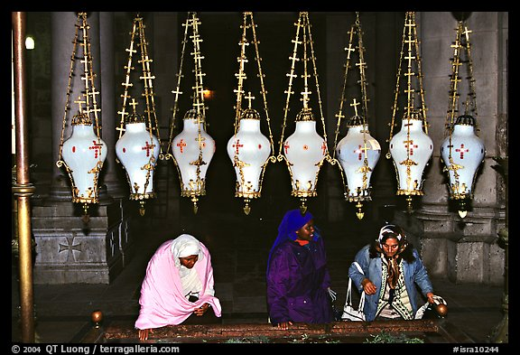 Women worshiping beneath hanging lamps inside the Church of the Holy Sepulchre. Jerusalem, Israel (color)