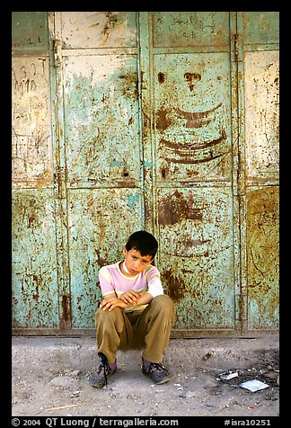 Young boy sitting in front of a closed store, Hebron. West Bank, Occupied Territories (Israel) (color)