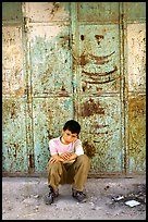 Young boy sitting in front of a closed store, Hebron. West Bank, Occupied Territories (Israel) ( color)