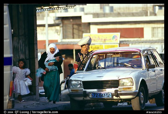 Women next to an old French Peugeot car, Hebron. West Bank, Occupied Territories (Israel) (color)