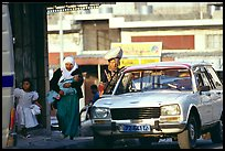 Women next to an old French Peugeot car, Hebron. West Bank, Occupied Territories (Israel) ( color)