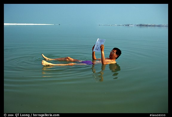 Visitor reading while floating in the Dead Sea. Israel (color)