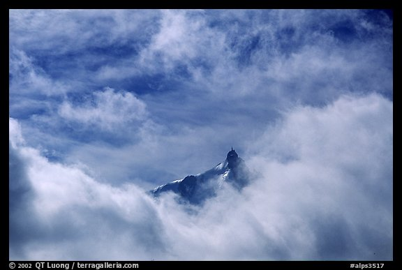 Aiguille du Midi summit emerges from the clouds. Alps, France (color)