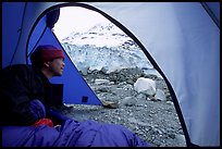 Visitor in  tent looking outside to Lamplugh Glacier. Glacier Bay National Park, Alaska (color)