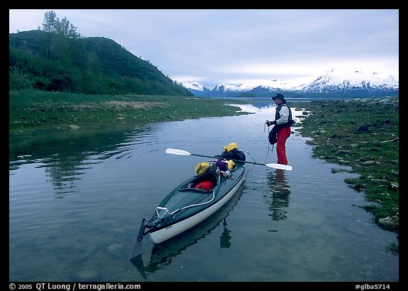 Kayaker tows kayak into a shallow tidal channel into Scidmore Bay. Glacier Bay National Park, Alaska (color)