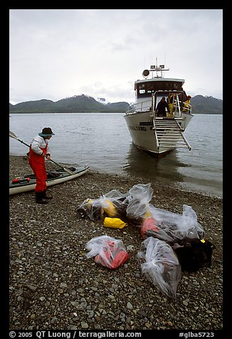 Kayaker standing with gear wrapped in plastic bags after drop-off. Glacier Bay National Park, Alaska (color)