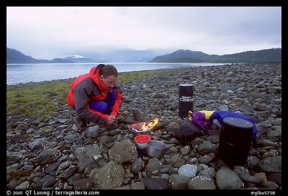 Kayaker firing up the stove,  Muir Inlet. Glacier Bay National Park, Alaska (color)