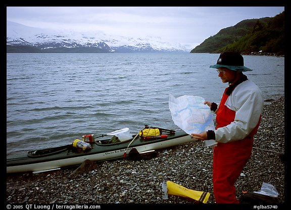 Kayaker looking at the map, East Arm. Glacier Bay National Park, Alaska (color)