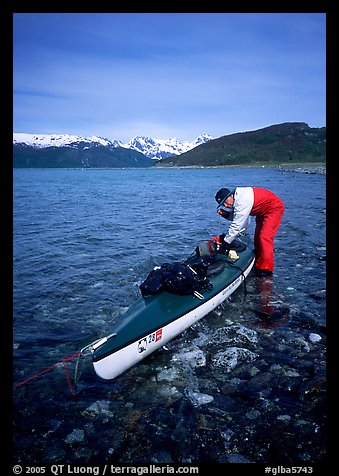 Kayaker tying up gear on top of the kayak,  East Arm. Glacier Bay National Park, Alaska (color)