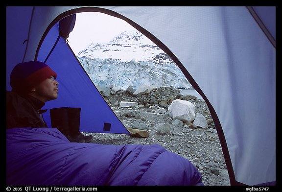 Camper lying in sleeping bag looks at Lamplugh Glacier. Glacier Bay National Park, Alaska (color)