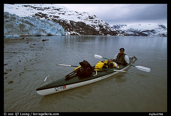 Kayaker sitting in loaded double kayak near Lamplugh Glacier. Glacier Bay National Park, Alaska (color)