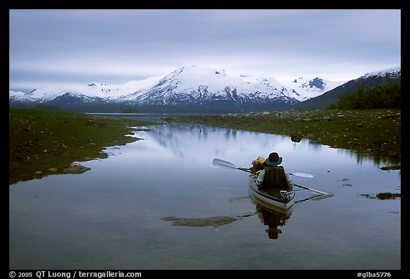 Kayaker paddles in  a shallow tidal channel into Scidmore Bay. Glacier Bay National Park, Alaska (color)