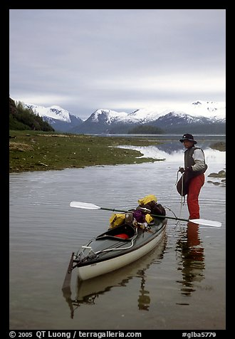 Kayaker standing in Scidmore Bay next to a shallow tidal channel. Glacier Bay National Park, Alaska (color)