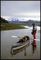 Kayaker standing in Scidmore Bay next to a shallow tidal channel. Glacier Bay National Park, Alaska