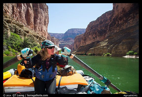 Woman rows raft on calm section of Colorado River, Marble Canyon. Grand Canyon National Park, Arizona (color)