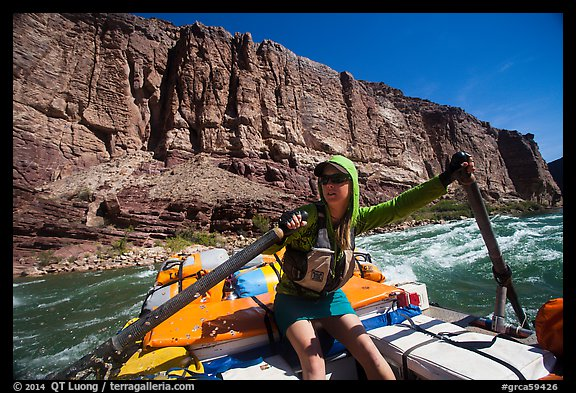 Woman stirring raft with oars in rapid. Grand Canyon National Park, Arizona (color)