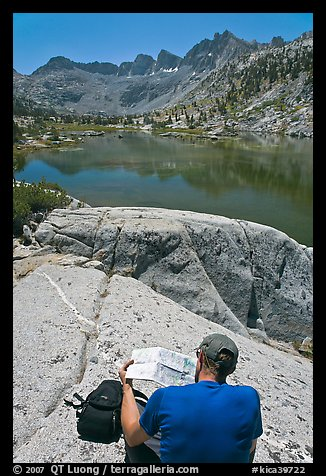 Hiker looking at map in front of lake, lower Dusy Basin. Kings Canyon National Park, California (color)