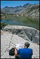 Hiker looking at map in front of lake, lower Dusy Basin. Kings Canyon National Park, California