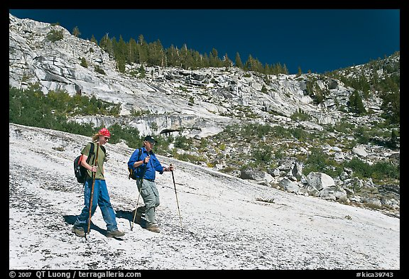 Father and son hiking on granite slab, Le Conte Canyon. Kings Canyon National Park, California (color)