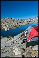 Man looking out from tent above lake, morning, Dusy Basin. Kings Canyon National Park, California (color)