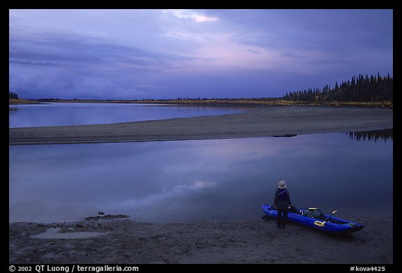 Standing next to the canoe on a sand bar, evening. Kobuk Valley National Park, Alaska (color)