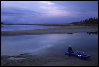 Standing next to the canoe on a sand bar, evening. Kobuk Valley National Park, Alaska