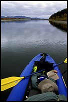 Canoeist reading a book while floating downriver. Kobuk Valley National Park, Alaska