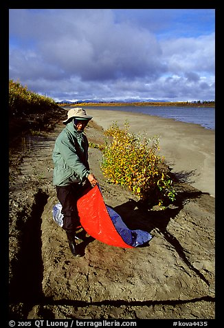 Camper folding the tarp while breaking camp. Kobuk Valley National Park, Alaska (color)